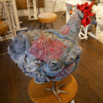 A grey and red chicken footstool