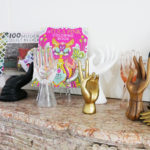 Tula Pink's mantle features a collection of hand statues that hold up two of her books.