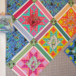 A corner of a quilt work in progress featuring Tula Pink's All Stars fabric collection.