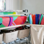 A quilt featuring Tula Pink's solid fabric collection is being stitched on her long arm quilting machine.
