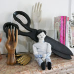 The mantle in Tula Pink's office features a collection of hand statuary, curios, and books.