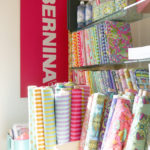 Tula Pink's All Stars fabric shares a corner with a Bernina sewing machine sign.