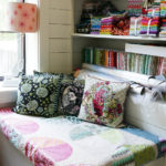 A cozy nook features three Tula Pink needlepoint pillows.