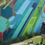 Phil Shafer debates on what colors to add to his mural in downtown Kansas City.