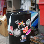 A garbage can is covered in Sike Style stickers in Phil Shafer's studio.