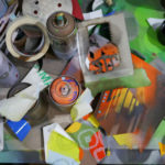 Work table full of spray paint, hexagons and stencils in Phil Shafer's studio.