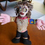 A handmade doll featuring a heavily beaded face.