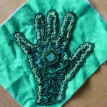 A green and blue beaded handprint, a part of a larger project that Nedra is working on.