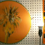 A Seth Smith palm tree painting is hung next to a coordinating level in his studio.