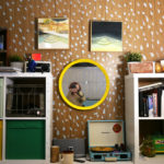 A bookcase wall in Seth's studio is filled with trinkets, books, and records, as well as two of Seth's pool paintings.