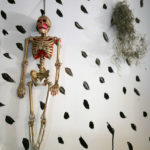 A gold and pink skeleton hangs on a polka dotted wall in Seth Smith's studio.