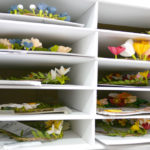 A file cabinet holds stacks of flower wreaths waiting to be shipped.