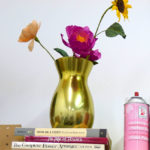 A stack of inspirational books topped with a paper floral bouquet in Grace D. Chin's studio.