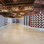 A corridor or Luke's quilts flow through an exhibition space.