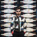 Designer Luke Haynes poses in front of his quilt - while wearing a coordinating patchwork shirt.