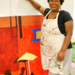 Glyneisha stands next to her current work in progress, a bright red collage based on a scene from the movie Do The Right Thing.