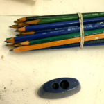 A bundle of drawing pencils sit next to a sharpener and eraser.