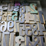 A tray full of letterpress numbers are tinted with the colors of recently used ink.