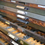 Drawers filled with different typefaces awaiting their turn in a letterpress design.